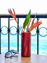 Sunglasses on a table with a red vase with bird of paradise inside with a beach and ocean background