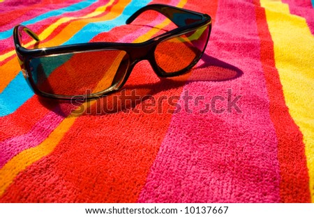 sunglasses on bright beach towel