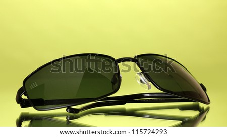 Sunglasses on green background