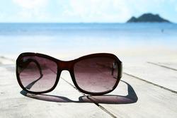 Sunglasses over the beach and blue sky