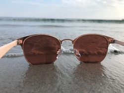 Sunglasses overlooking the Ocean Waves and water reflection