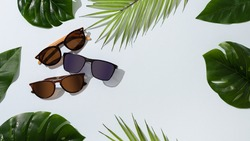 Sunglasses sale. Summer sale-out offer. Sunglasses in wooden frame on yellow background. Copy space for text. For banner
