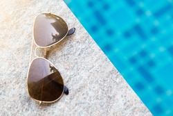 Sunglasses with natural light on poolside.