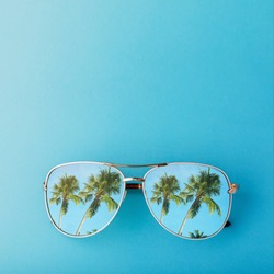 Sunglasses with palm trees reflected in them and space for text, top view