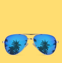sunglasses with palms isolated on yellow background.