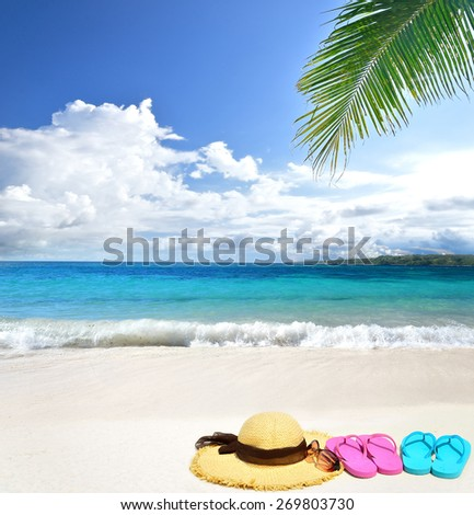 Sunhat with sunglasses and flip flops at the tropical beach -- Tropical beach vacation and travel concept
