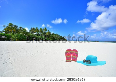 Sunhat with sunglasses and flip flops at the tropical white sandy beach -- Tropical beach vacation and travel concept