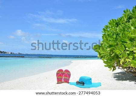 Sunhat with sunglasses and slippers at the tropical white sandy beach -- Tropical beach vacation and travel concept