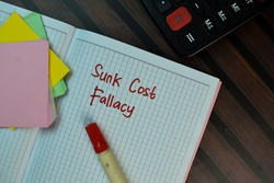 Sunk Cost Fallacy write on a book isolated on Wooden Table.