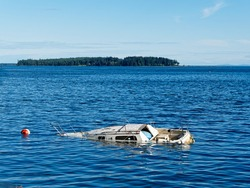 Sunken boat floats in the coastal waters near shore of Sidney BC