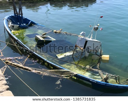 sunken fishing boat in a harbor, great pic to sell insurance or just as a beautiful background.