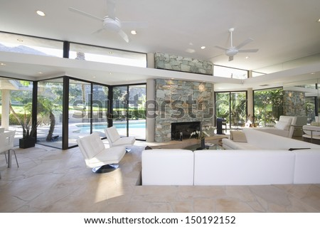 Sunken seating area and exposed stone fireplace in spacious living room with view of swimming pool at home