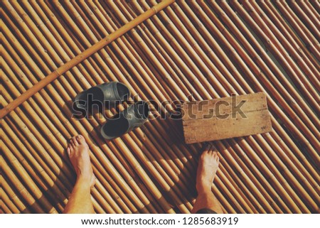Sunlight and shadow on surface of Asian man's feet with rubber sandals and little wooden bench on bamboo litter in homestay with vintage tone, lifestyle on ecotourism concept