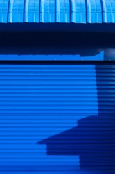 Sunlight and shadow on surface of automatic blue roller shutter door with steel awning in vertical frame