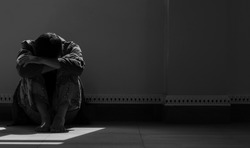 Sunlight and shadow on surface of hopeless man sitting alone with hugging his knees on the floor in empty dark room in black and white style
