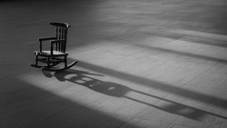 Sunlight and shadow on surface of  the old vintage little wood rocking chair on wooden tile floor in black and white style, concept of loneliness, alone, thinking of people who have gone far far away