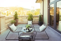 sunlight and table and chairs in modern balcony