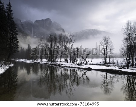 sunlight  breaking through winter fog and clouds on a quiet  snowy morning in yosemite valley,california.