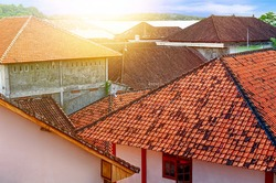 Sunlight from dawn over old houses with tiled roofs. Morning in a small quiet suburb. View from above. City landscape vintage. Asia, Bali.