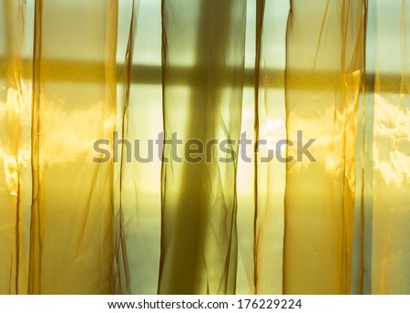 Sunlight from outside window streams into a room through thin golden silky net curtains