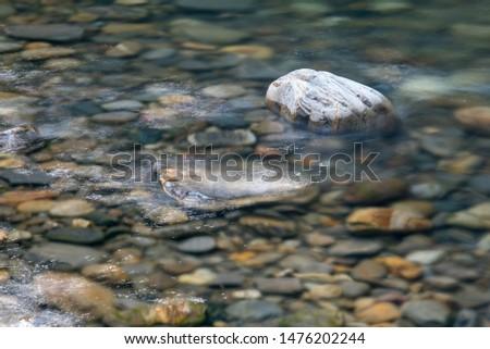 Sunlight glistening in erratic, random patterns on water flowing over rocks in a mountain stream