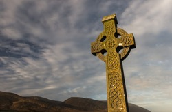 Sunlight hitting celtic cross gravestone at dawn  in rural County Kerry, Ireland