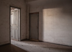 Sunlight is falling through an empty room of an old, deserted building.