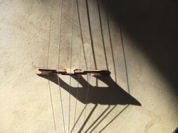 Sunlight on banjo shows strings and shadows of strings revealing texture of the instrument.