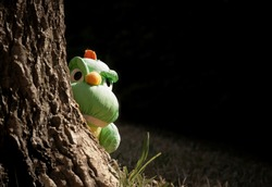 Sunlight on little green dinosaur plush doll in peek gesture behind a big tree trunk in the garden, close up with copy space
