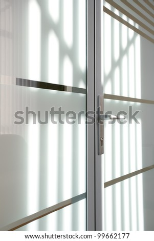 sunlight on the glass door with metal trim and metal handle