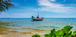 Sunlight over the tropical beach with coconut palm and Fishing boat at Chao Lao, Chanthaburi, Thailand, Is paradise beach in Thai, the foreground of bush trees and amazing cloudy in Morning.