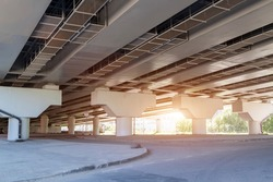 sunlight penetrates under overpass. Road construction Highway overpass bridge concrete structure with columns in city