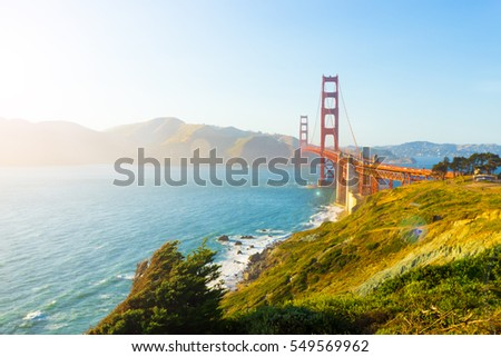 Sunlight provides high key highlights, lens flare over Marin Headlands with Golden Gate Bridge seen over rocky coastline at Fort Point during sunset in San Francisco, California. Horizontal copy space