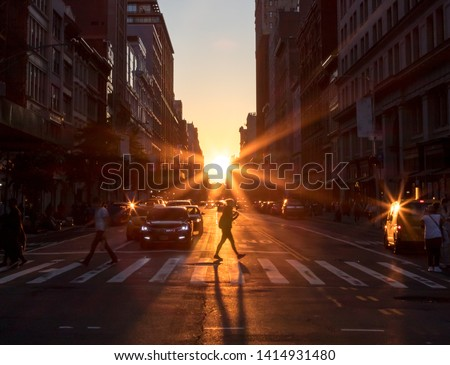 Sunlight shines on a woman crossing the intersection with a long shadow cast on the streets of Midtown Manhattan in New York City NYC stock photo
