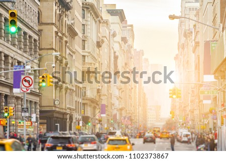 Sunlight shines on Broadway in New York City with people and cars lining the street through Midtown Manhattan #1102373867