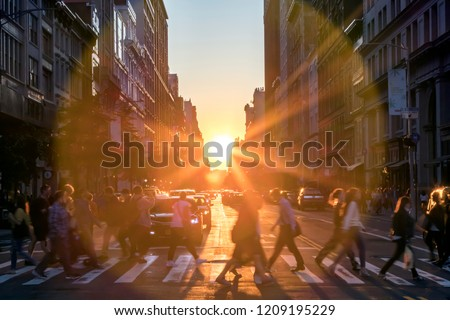 Sunlight shines over the buildings and people of a busy Midtown Manhattan street scene in New York City NYC