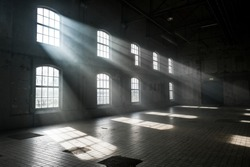 Sunlight shining throuh the windows of an old abandoned industrial warehouse building