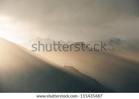 Sunlight squeezes in at an angle over the Himalaya mountains, a landscape view seen from Bhimakali Temple in Sarahan, Himachal Pradesh, India