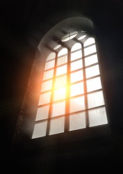 Sunlight through the glass of an antique arched gothic window