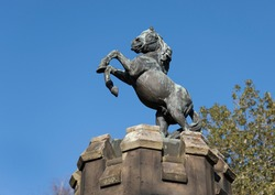 Sunlit bronze statue of a rearing stallion on top of the southern castellated turret at the gateway to Ford Castle with a background of clear blue sky.