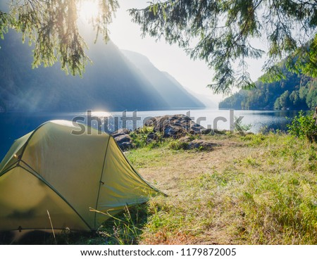Sunlit camping tent at scenic campsite on a lake shore with mountain range in background - wild camping in Norway #1179872005