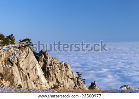 Sunlit cliffs and sea in clouds. Crimean mountains.