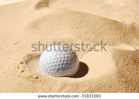 Sunlit golf ball with shadow in unraked sand trap.  Macro with shallow dof. - stock photo
