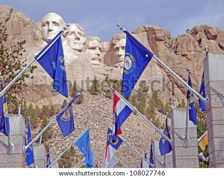 Sunlit images of George Washington, Thomas Jefferson, Theodore Roosevelt and Abraham Lincoln and the flags of the States at Mt. Rushmore National Memorial, Keystone, South Dakota