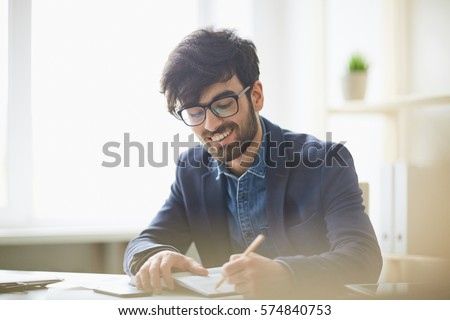 Sunlit portrait of young creative mn in glasses and business casual wear writing something down to notebook, smiling and looking pleased sitting at desk in modern office