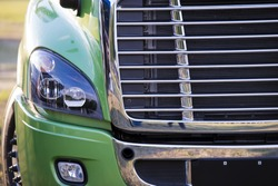 Sunlit powerful modern stylish and comfortable green big rig semi truck of latest model commercial long-distance transport shiny chrome grille efficient headlight in parking lot waiting for cargo.
