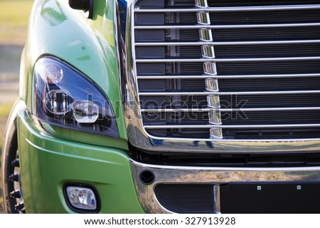 Sunlit powerful modern stylish and comfortable green big rig semi truck of latest model commercial long-distance transport shiny chrome grille efficient headlight in parking lot waiting for cargo. #327913928
