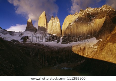 Sunlit rocks on snow-covered mountain