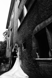 Sunlit romantic married couple on bridge with flowers leaning against old wall b&w