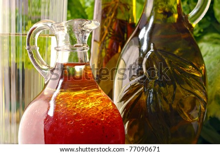Sunlit still life of raspberry vinaigrette salad dressing in glass cruet with bottles of olive oil and salad greens in background.  Macro with shallow dof.
